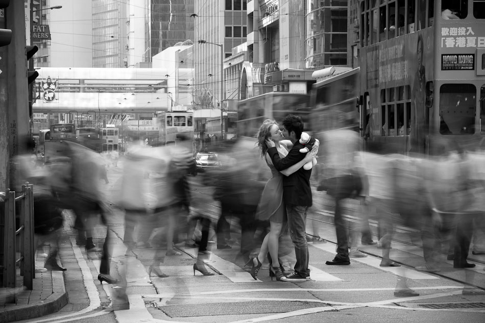 Louis Kwong Photography's  home page photo. A couple kissing in the zebra crossing in Hong Kong